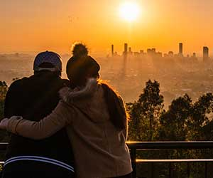 couple watches sunrise over city